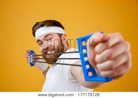 Portrait of a strong athletic guy sports man stretching expander over orange background