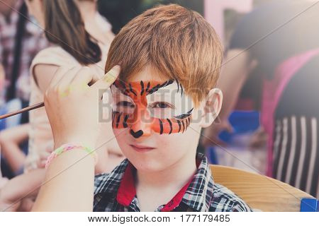 Child with tiger face art painting. Children holiday, birthday party entertainment.