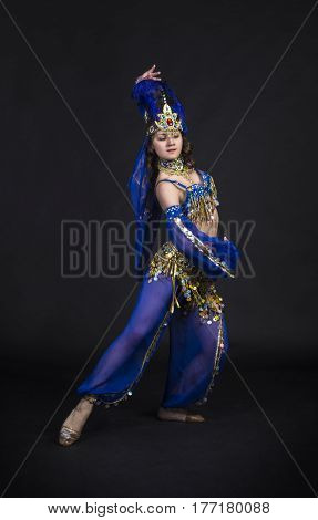Young,smiling girl dancing the Eastern dance. Belly dance stage performance. Shooting in Studio on a dark background.