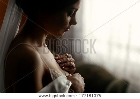 The tenderness bride stands near the window