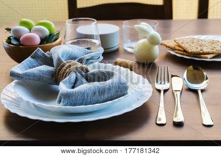 Spring dinner place setting . Beautiful Easter table decoration white decorative bunny, colorful eggs, line napkin cutlery and dinnerware on wooden background. Happy Easter concept.