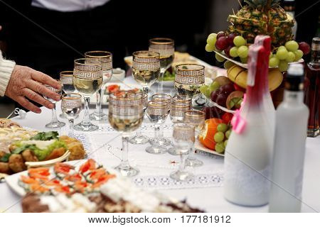 The buffet table with snacks and alcohol are near house