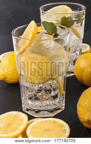 sparkling mineral water with ice and lemon slices in a glass