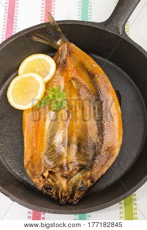 warm smoked kipper with lemon and parsley in a cast iron pan