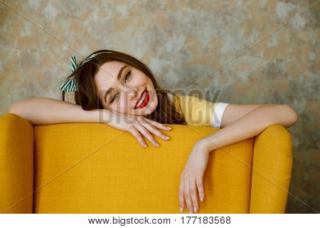 Close up portrait of a smiling happy pin up girl laying on chair