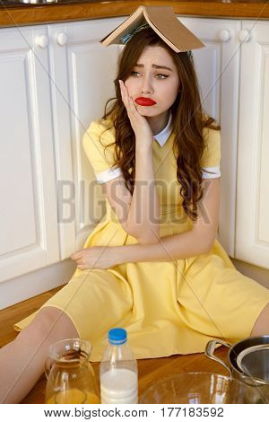 Picture of sad young pin-up woman with red lipstick sitting on floor at kitchen and cooking with book on head. Looking aside.