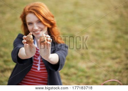 Portrait of a smiling young woman with long ginger hair showing two painted easter eggs outdoors