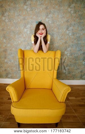 Portrait of a smiling pretty pin up woman leaning on chair indoors