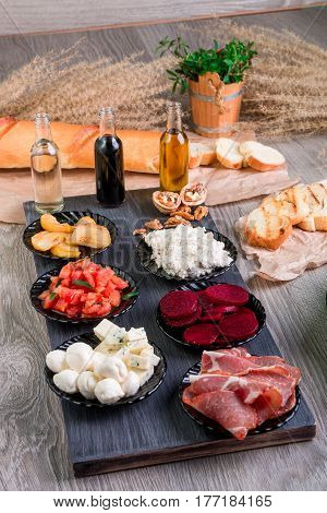 Ingredients On Plate For Preparation Bruschetta Near Bottle With Sauce. Italian Cuisine Food Antipas