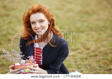 Attractive young red head girl holding picnic basket with easter eggs outdoors