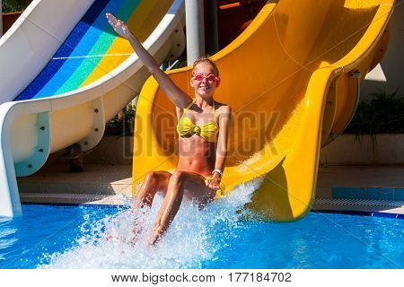 Swimming pool slides for children on water slide at aquapark . Summer kid holiday outdoor. Happy little girl hand up in aqua park.