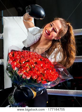 Boxing woman workout in fitness class. Boxer wearing gloves to box and tower in ring. Girl with bouquet flowers sitting in corner of boxing ring.