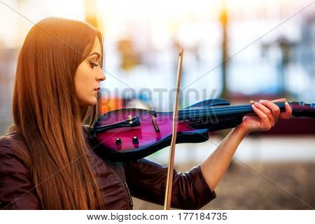 Busker woman perform music on violin in park outdoor. Sad beautiful girl performing jazz on city street . Spring outside with background.