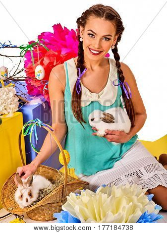Easter dresses for women. Girl holding bunny and eggs. Woman with holiday hairstyle and make up touch rabbit in basket with flowers. Adults at the festival. Breeding of domestic animals.