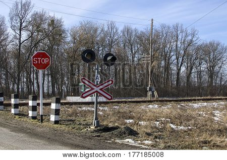 Railroad crossing on spring forest and sky background