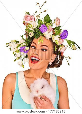 Easter girl holding bunny. Woman with holiday spring flowers hairstyle and make up with fake eyelashes. Female makes squint eye for fun. She has strabismus. Breeding of domestic animals.