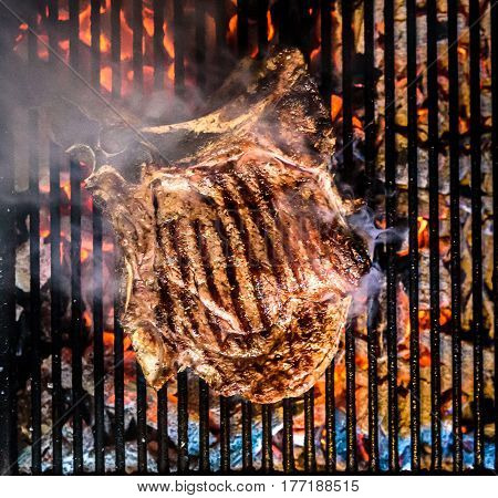 Grilling Big T-bone Steak On Natural Charcoal Barbecue Grill.