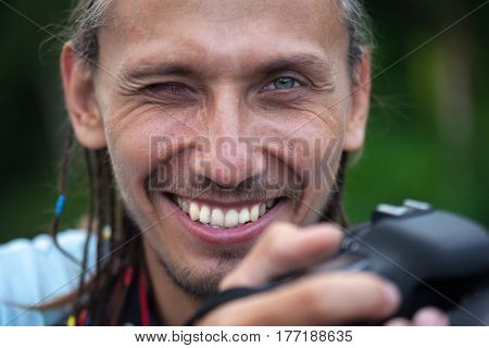 Young man with a professional camera smiling and enjoying a sunny summer day in the park. Smiling looking into the lens.