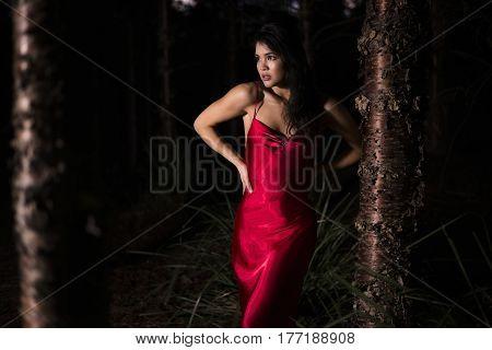 Beautiful Young Woman In The Gardens Wearing A Long Silk Red Dress.