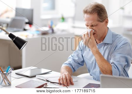 Give me napkin. Ill male person sitting in semi position in the office blowing his nose while keeping eyes closed