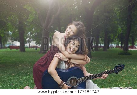 Young boho hippie girls with guitar in park. Friendship and fun