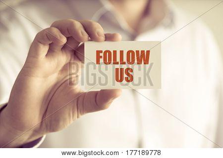 Businessman Holding Follow Us Message Card