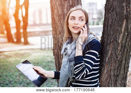Young woman with digital tablet in hand talking on mobile phone with boyfriend before a meeting with it. Attractive blonde girl hold touch pad while calling with cell telephone to darling