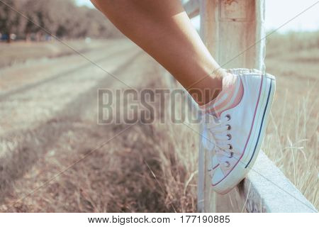 Woman legs wearing Woman legs wearing sneakers sitting on the fence. The concept of travel adventure freedom claws over obstacles.