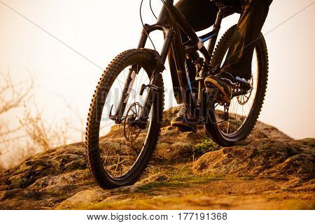 Enduro Cyclist Riding the Bike Down Rocky Hill at Sunset. Close up Extreme Sport Concept. Free Space for Text.