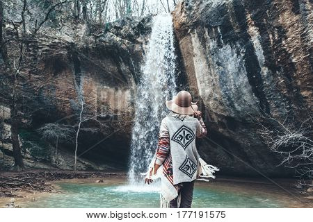 Boho woman wearing hat and poncho standing by the waterfall and looking at it. Cold weather, winter hiking. Wanderlust photo series.