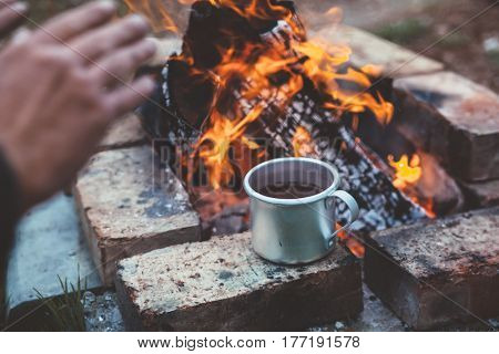 Traveler warming his hands by the campfire outdoors. Tea or coffee in aluminum mug on background. Camping detail, travel lifestyle photo.