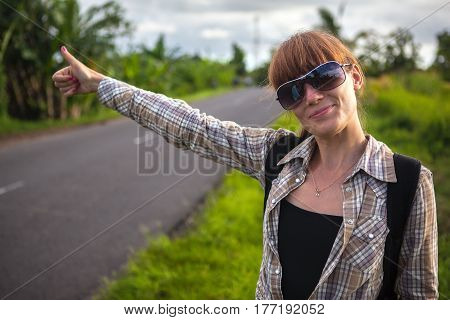 Young beautiful girl is traveling hitchhiking. Stands on the road with a good mood and catches the car