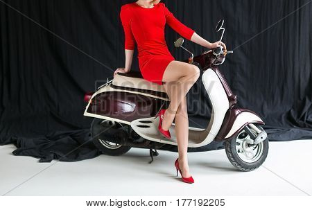 the charming sexy young woman in a short red dress and red shoes on the scooter motorbike on a black background in studio. Retro shot. Fashion art photo.