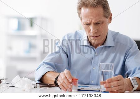Drink or not. Very serious male person wearing blue shirt holding glass of water while wrinkling his forehead