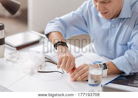 Make effort. Attentive male person wearing blue shirt keeping his arms on the table holding jar with pills in hands