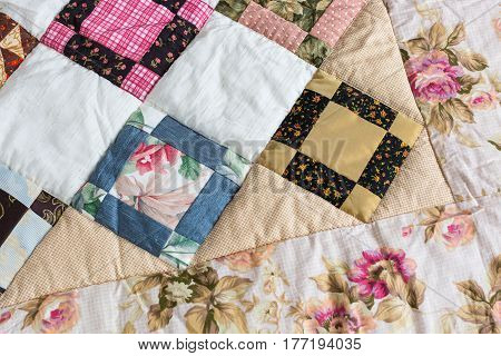 Part of color patchwork quilt with vintage flowers pattern as background. Colorful Scrappy blanket. Handmade. Hobby Concept.
