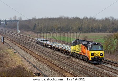 DENCHWORTH, UK - MARCH 25: A Colas operated train heads towards Bescot depot with a near empty load of wagons on March 25, 2015 in Denchworth. Colas operate 10 class 70 locos from a total fleet of 48.