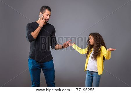 A black father talking on his phone while his young daughter looking at him questioningly with her arms raised up