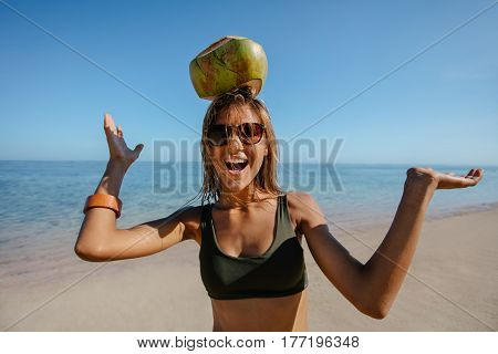 Happy Woman Balancing A Coconut On Her Head At The Beach
