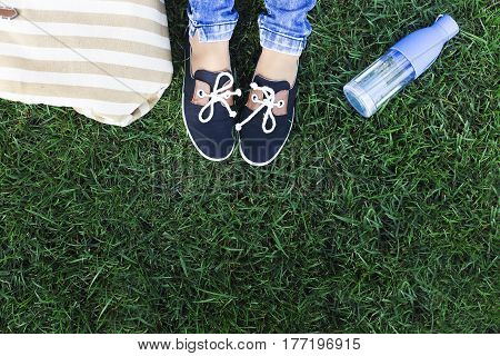 Feet of a young girl on a background a green grass with bottle of water and bag. Travel and holliday concept