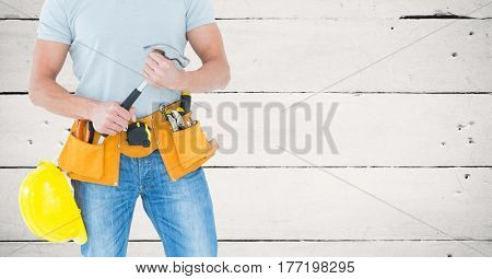 Digital composite of Carpenter with hammer against white wood panel