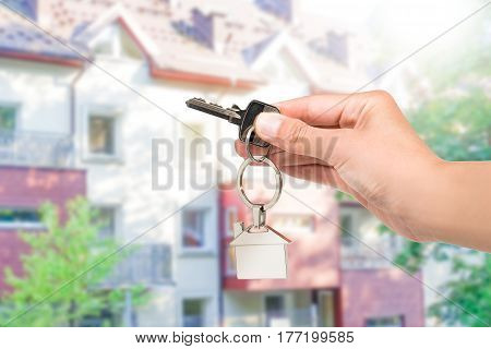 Real estate agent giving house key with a keychain home form. Blur background.