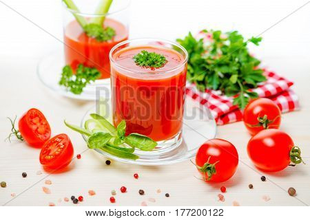 Tomato Juice In Transparent Glasses With Parsley, Basil,  Cucumber And Napkin On Light Wooden Backgr