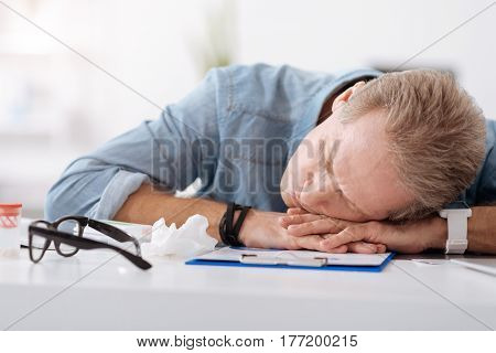 Dinner sleep. Tired man wearing jeans shirt keeping both hands on the table putting his head on hands