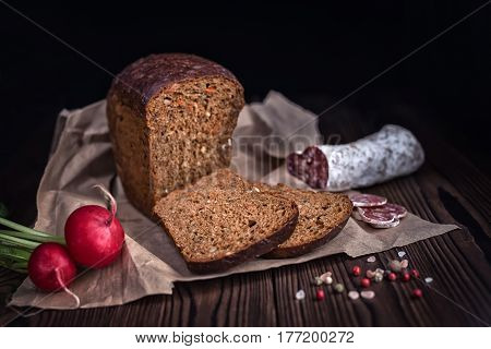 Sliced Brown Bread, Salami, Radish And Dry Pepper On Paper Over Wooden Background, Rural Style, Clos