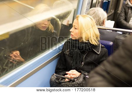 Thoughtful lady riding on a subway and looking out the window. Reflection of her face can be seen in the window.