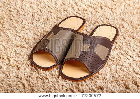 Men's leather slippers stand on a mat