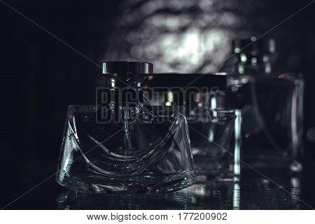 Perfumery. Three bottle of female perfume over grey background
