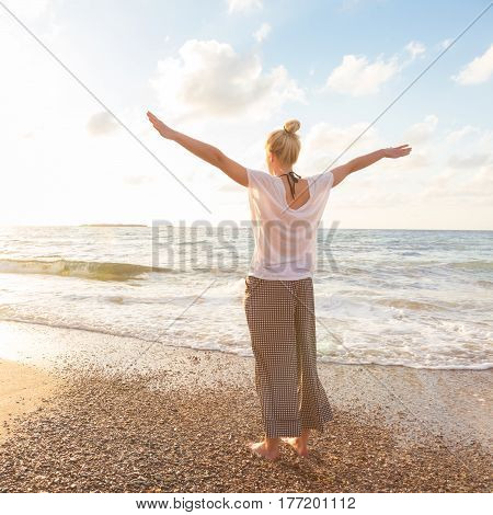 Relaxed woman, arms rised, enjoying sun, freedom and life an beautiful beach in sunset. Young lady feeling free, relaxed and happy. Concept of vacations, freedom, happiness, enjoyment and well being.