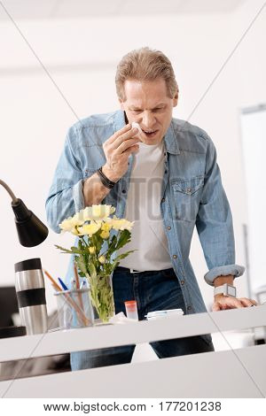 That is allergen. Angry man wearing casual clothes, wiping his nose while looking at flowers